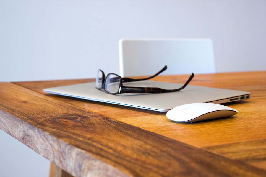 glasses resting on laptop on a table