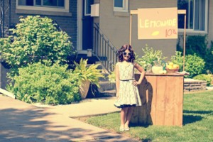 Young girl selling lemonade at stand